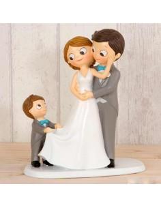 Figura de novios sonriendo con un niño sujetando el traje a la novia