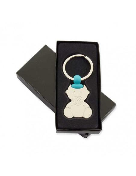 Llavero bebé con chupete y un detalle azul, en su caja de presentación.