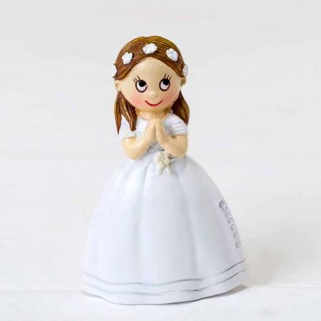 Imán niña vestida de blanco con una corona de flores en el pelo, lleva las manos juntas rezando