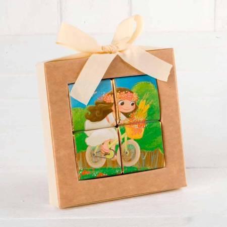 Original estuche con 4 napolitanas de chocolate cuyo envoltorio forma un divertido puzle, de una niña en bicicleta